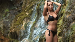 Beautiful young girl in bathing suit standing at the foot of the waterfall Stock Footage