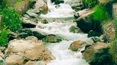 Small mountain river with artificial rapids made of cobblestones - stock footage