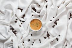 Cup of coffee on a white silk fabric. Espresso and scattered beans. Top view Stock Photos
