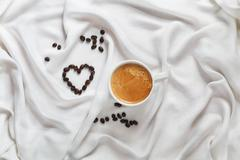 Cup of coffee on a white silk fabric. Espresso and scattered beans. Top view - stock photo