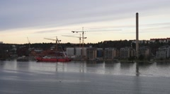 Floating on the river by buildings, tower cranes and red ship Stock Footage
