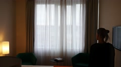 Woman in a hotel room going towards the window, opening curtain and looking at Stock Footage