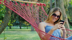 Young woman in sunglasses resting in a hammock, enjoy telephone Stock Footage