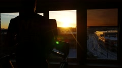 Back view of a man running on a treadmill near the window in rays of sunset Stock Footage