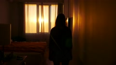 Silhouette of a girl going towards the window and unveiling curtains. Stunning Stock Footage