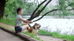 Girl with english bulldog in park near the pond Stock Footage