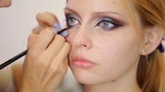 Make-up artist applying make up with a brush on model's face Stock Footage