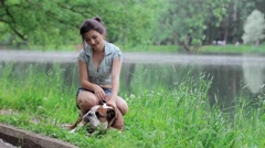 Girl playing with english bulldog near the pond Stock Footage