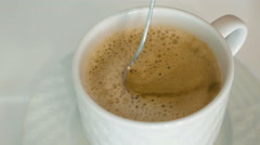 A person is stirring hot coffee with a foam Stock Footage