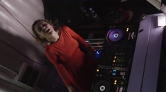 Dj girl in red dress energy dance at turntable in nightclub. Look in camera Stock Footage