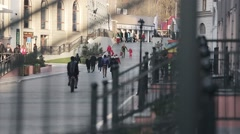 View at crowded street, walking people, buildings, snowboarders. Sunny evening Stock Footage