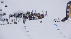 Snowboarder in helmet high jump from springboard at ski resort. Snowy mountains - stock footage