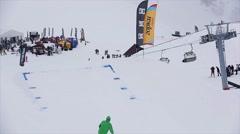 Snowboarder in helmet jump from springboard at ski resort grab board in air Stock Footage