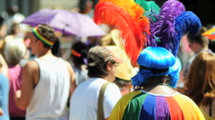 Supporter watches Gay pride parade in colorful rainbow costume feathers GLBT - stock footage