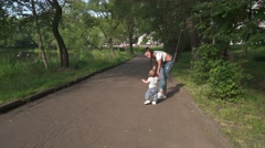 mother teaching baby to walk in the park - stock footage