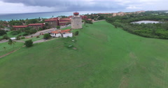 Drone flies over a green field to an old stone tower. Bird's-eye view at city Stock Footage