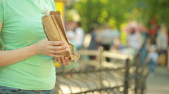 Girl drinking from a paper bag in the street. anti-social behavior Stock Footage