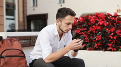 Young attractive male in his 20s sitting on a bench and typing a message Stock Footage