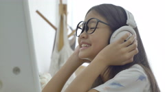 4K : Attractive Asian girl listening music on computer with headphone - stock footage
