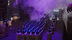Vial of liquid for electronic cigarettes at stand in nightclub. Spotlight. Steam - stock footage