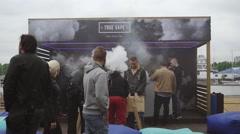 Men smoke electronic cigarette on street. Vaper festival. Play table soccer - stock footage