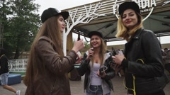 Girls with red lips and cap smoke electronic cigarette on street. Vaper festival - stock footage
