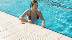 A female is walking on the side of the pool Stock Footage