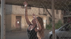 Sexy woman behind the wire fence Stock Footage