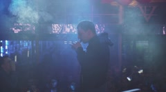 Man smoking electronic cigarette on stage of nightclub. Challenge. Steam. People - stock footage