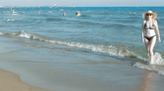 A woman flawlessly walks towards the shore Stock Footage