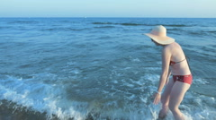 Female loses her sun hat walking alongside the sea Stock Footage