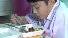 Asian child in student uniform eating food in plastic foam box Stock Footage