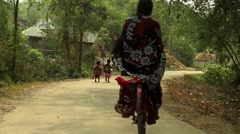 Little boy and girl walk along a village road in India Stock Footage