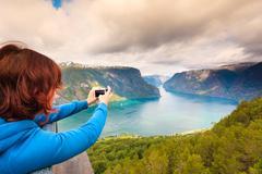 Tourist taking photo from Stegastein viewpoint Norway - stock photo