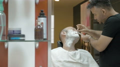 Barber is shaving his client in old fashion manner Stock Footage
