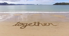 Aerial of the word together in the sand Stock Footage