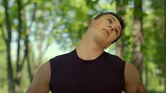 Fitness man warm up neck outdoor. Closeup of fit man stretching in park Stock Footage