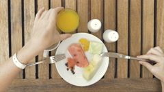 Lady is using utensils to cut meal in small bites Stock Footage