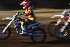 Motocross bikers on dirt track Stock Photos