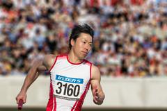 Japanese male sprinter running on track Stock Photos