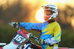 Motocross biker on dirt track - stock photo