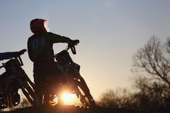 Motocross bikers on dirt track - stock photo