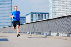 Young Caucasian man running in metropolitan area - stock photo