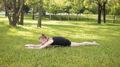 Girl teenager sitting in the splits on the grass and exercise Stock Footage