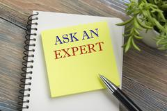 Ask an expert. Notepad with message, pen, reminder and flower. Office supplies Stock Photos