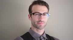 Stylish guy with eyeglasses on beige background - stock footage