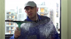 Cleaner man in blue uniform spray and wipe window with wiper tool Stock Footage