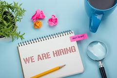 We are Hiring. Office desk table with notepad, pencil and coffee cup. Top view Stock Photos