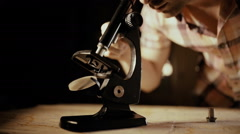 Man watch an object through a microscope Stock Footage