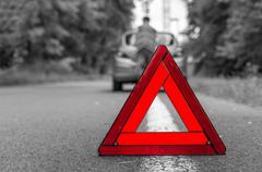 Unhappy driver and broken car on the road and red warning triangle - black an Kuvituskuvat